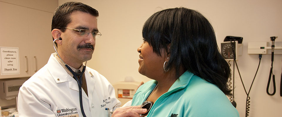 Mario Castro, MD, uses a stethoscope to check the heart rate of an African-American woman